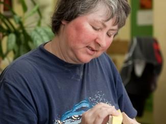 Eine Frau arbeitet in der Werkstatt mit Holz.