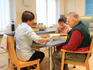 Betreuerin Julia Seppi, Regina Sanjath und Hermann Pfahnl bereiten das Abendessen zu