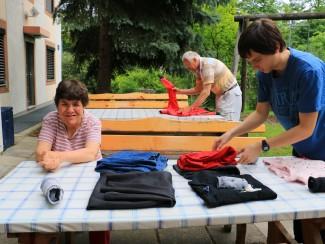 Rainer Sosen, Regina Sanjath beim Wäsche zusammenlegen, ein Zivildiener unterstützt