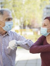 Two senior people greeting each other with elbows, alternative non-contact greeting during coronavirus epidemic, standing on the street in safe distance.