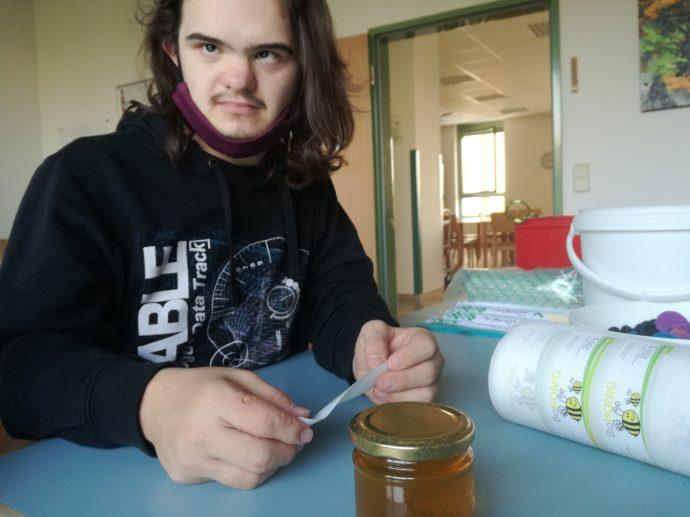 Herr Wejwoda beklebt die Honiggläser mit Etiketten